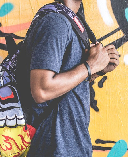 Student with backpack in front of mural
